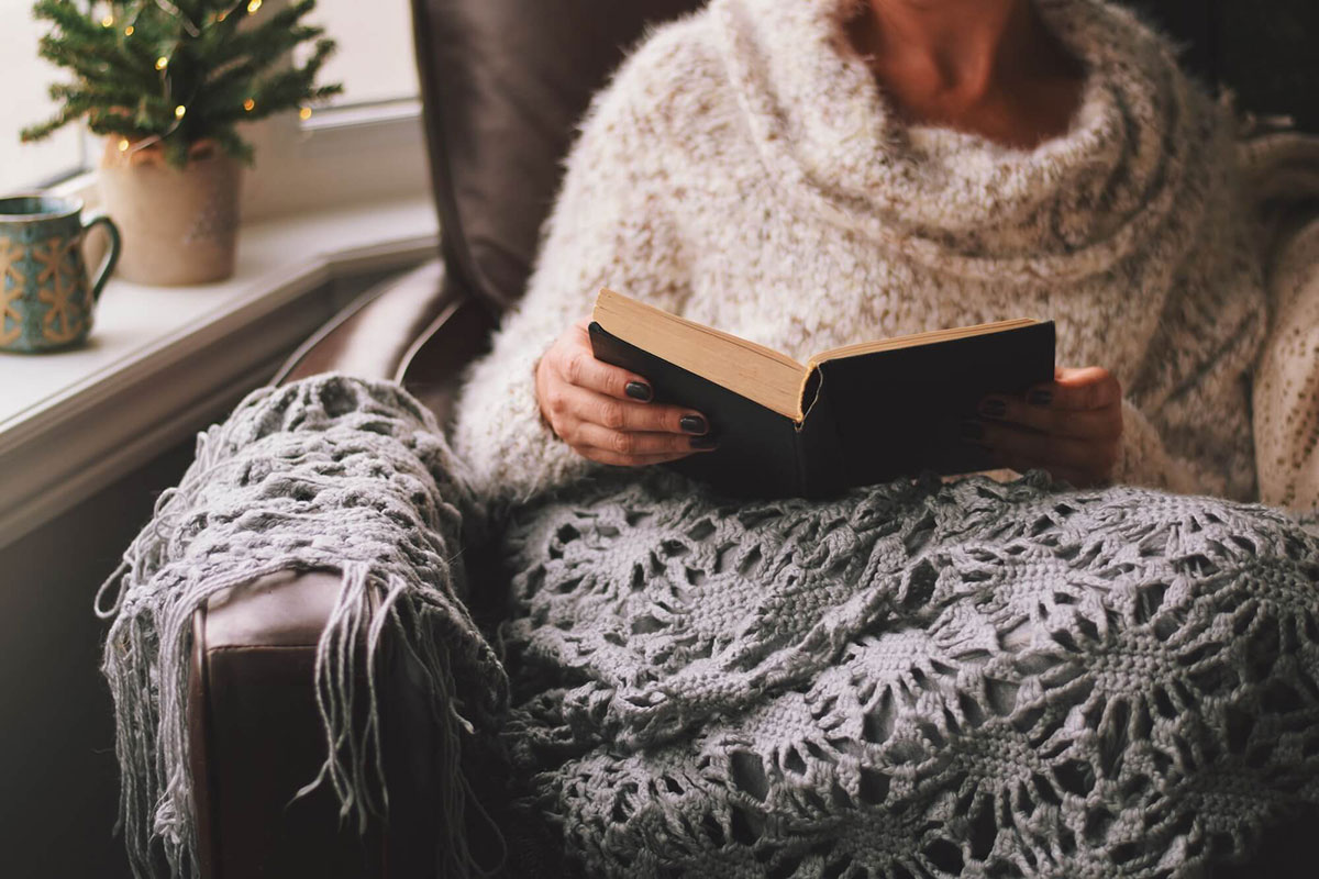 woman-in-a-warm-and-cozy-sweater-sitting-on-a-chai-YM2SPV7